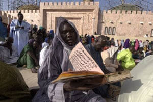 A member of the Mouride Brotherhood, a large Sufi order, reads a religious book outside the Great Mosque during the Magal festival celebrating the return from exile of its founder, the great marabout Sheikh Amadou Baba
