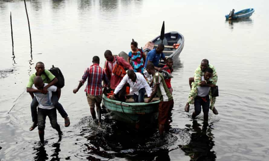 Boat guides carry people through polluted water in Ogoniland