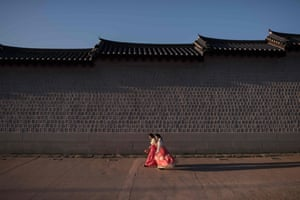 Women wearing traditional hanbok dress walk along a wall of Gyeongbokgung palace in Seoul, South Korea
