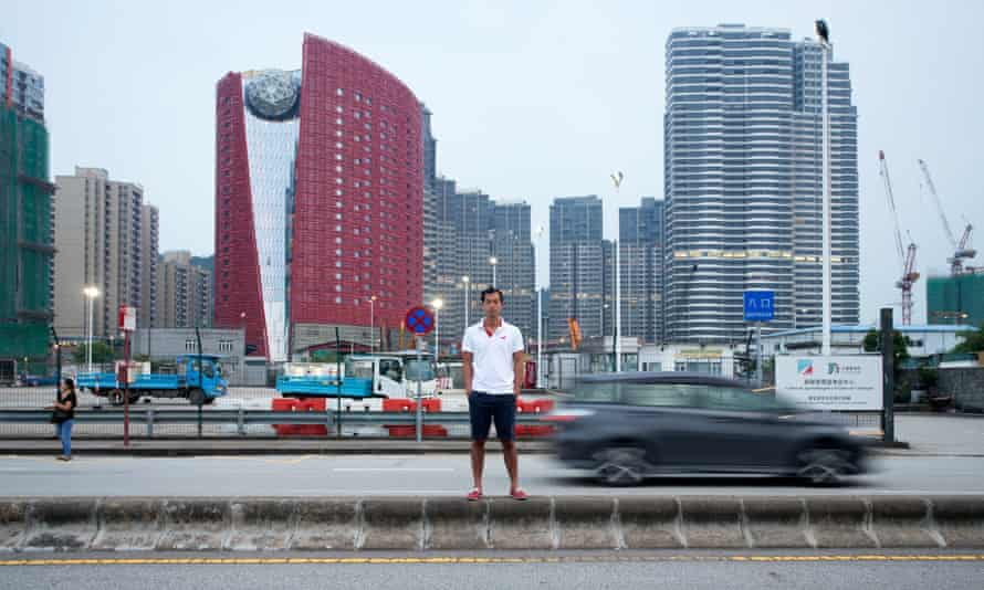 Daniel Yan standing outside The 13 Hotel surrounded by ordinary apartment buildings in Macau's Coloane neighbourhood