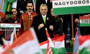 Viktor Orban greets supporters at the Hungarian parliament in Budapest on 15 March