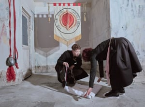 Contemporary issues, stories winner. Women fold a cloth in front of a banner reading 'Our toil doth sweeten others'