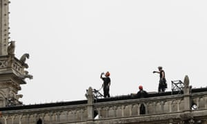 Workers stand on top of Notre Dame Cathedral