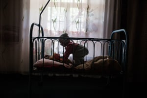 A one-year-old child left by her parents to be raised by her grandmother in Karabag, Batken Oblast. The grandmother, who is unable to give her round-the-clock care, has built a cage around her bed so she doesn't wander away