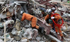 Rescue workers search for victims in the debris a day after an under-construction building collapsed in Sihanoukville.