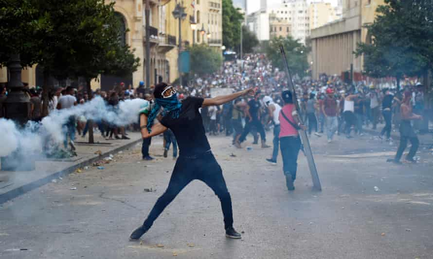 An anti-government protester throws a teargas canister back towards riot police during a clash with security forces in the area close to the parliament in Beirut.
