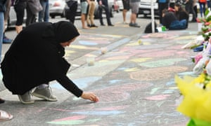A mourner draws on the pavement outside a mosque in Kilbirnie, Wellington, on Saturday.