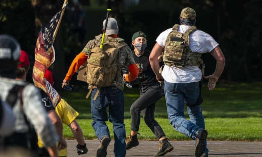 Rightwing demonstrators chase a Black Lives Matter protester after a pro-Trump caravan rally at the Oregon state capitol on 7 September 2020 in Salem.