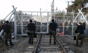 Macedonian police officers stand in front of a gate over as migrants wait behind at the Greek-Macedonian border