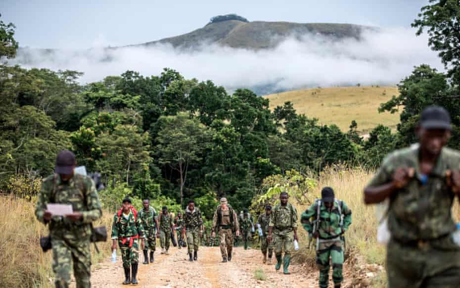 A rifleman of the 2nd battalion The Rifles regiment walks with Gabon national park rangers.