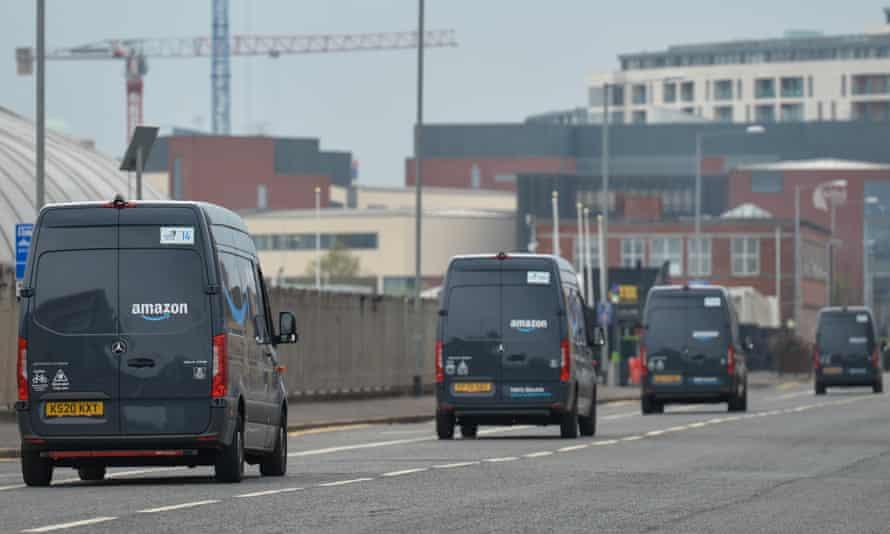 line of amazon vans on a road in belfast