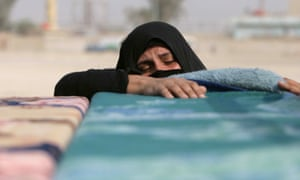An Iraqi woman stands by the coffin of a relative during the funeral of people found in a mass grave in Karbala, south of the Iraqi capital Baghdad, in 2008