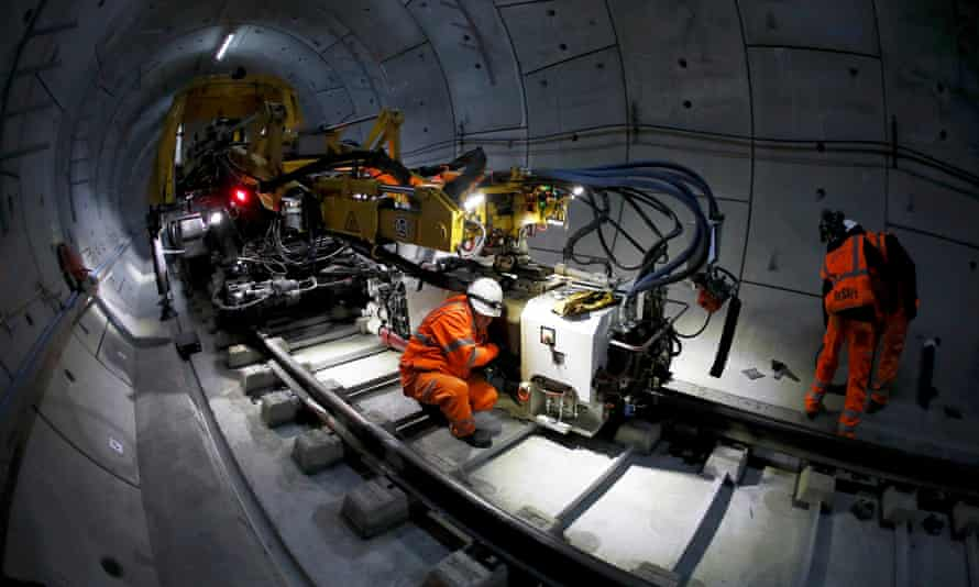 Workers lay railway track in a tunnel of the Crossrail project in east London, November 2016