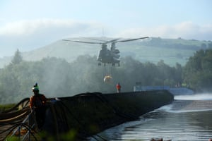 An RAF Chinook helicopter flies in sandbags to help repair a dam in Whaley Bridge, UK