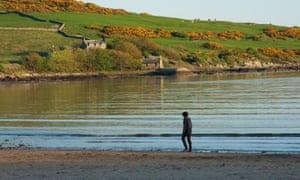 Man walking on sandy beach with hillside behind