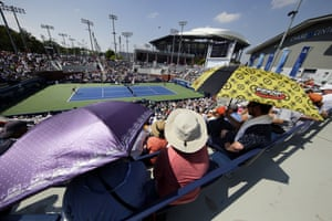 Fans use umbrellas to shelter from the sun as they watch the match between Victoria Azarenka and Daria Gavrilova.