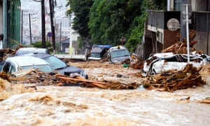 Cars damaged by floodwater as heavy rain continues in Hiroshima, Japan. Dozens of people have been killed.