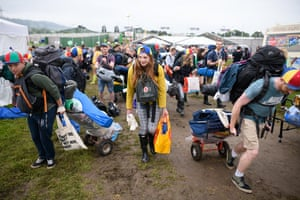 Glastonbury, UK. Festival-goers carry their belongings and tents to the camping areas as the gates are opened during day one of Glastonbury Festival at Worthy Farm in Somerset