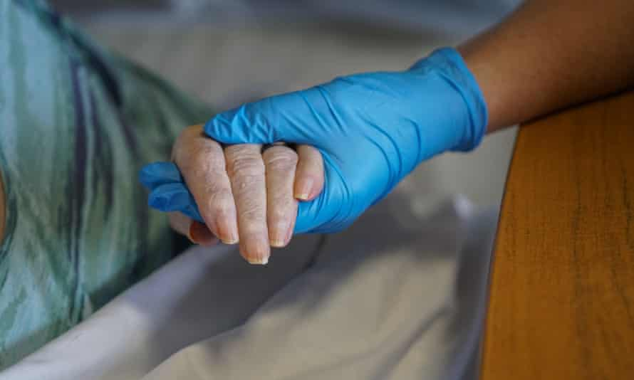 A woman holds her mother's hand in a care home