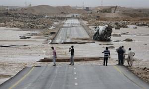 People look at a road torn apart by Cyclone Merkunu in Salalah, Oman