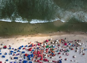 An aerial picture taken with a drone showing people spending time on the Barra da Tijuca beach in Rio de Janeiro