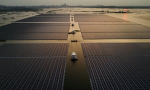 Chinese workers ride in a boat through a large floating solar farm project, billed as the largest in the world, under construction on a lake in collapsed and flooded coalmine in Huainan, Anhui province
