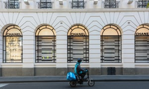 A food delivery rider rides past a Chanel boutique