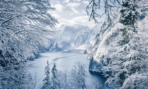 A frozen lake surrounded by snow-covered trees and mountains behind