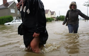 Residents walk through flood waters in North Cave, near Hull, in June 2007.