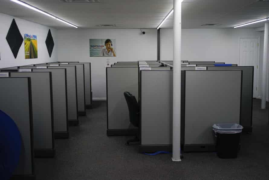 An empty call center office with gray cubicles.