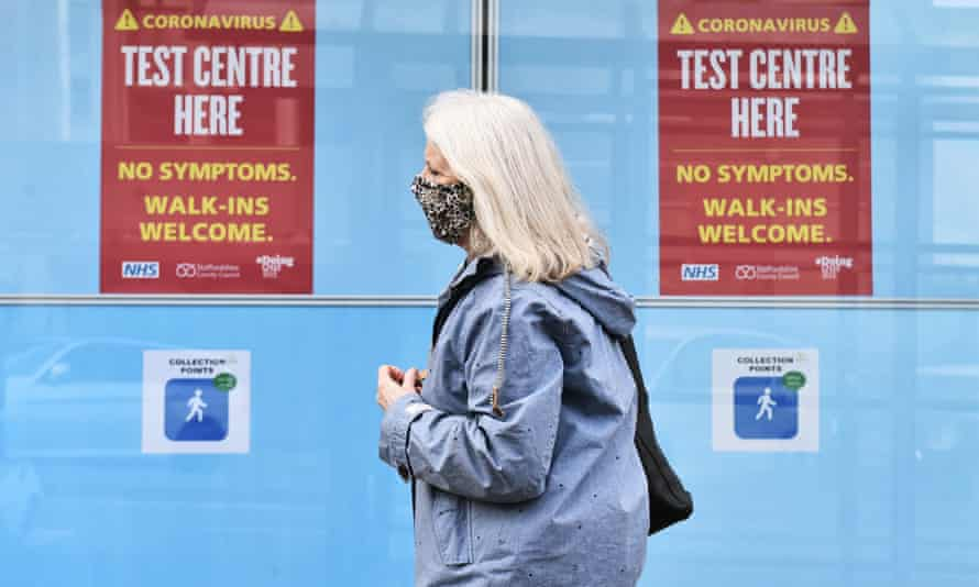 A lady wearing a mask walks past a walk in coronavirus test centre on May 12, 2021 in Newcastle-Under-Lyme,