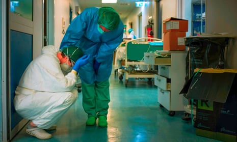 A nurse wearing PPE comforts another as they change shifts at Cremona hospital, Italy, in March.