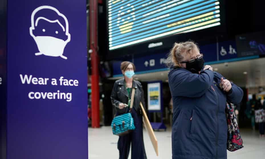 People wear face masks at the train station.