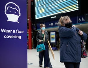 People wear face masks at the train station in Liverpool.