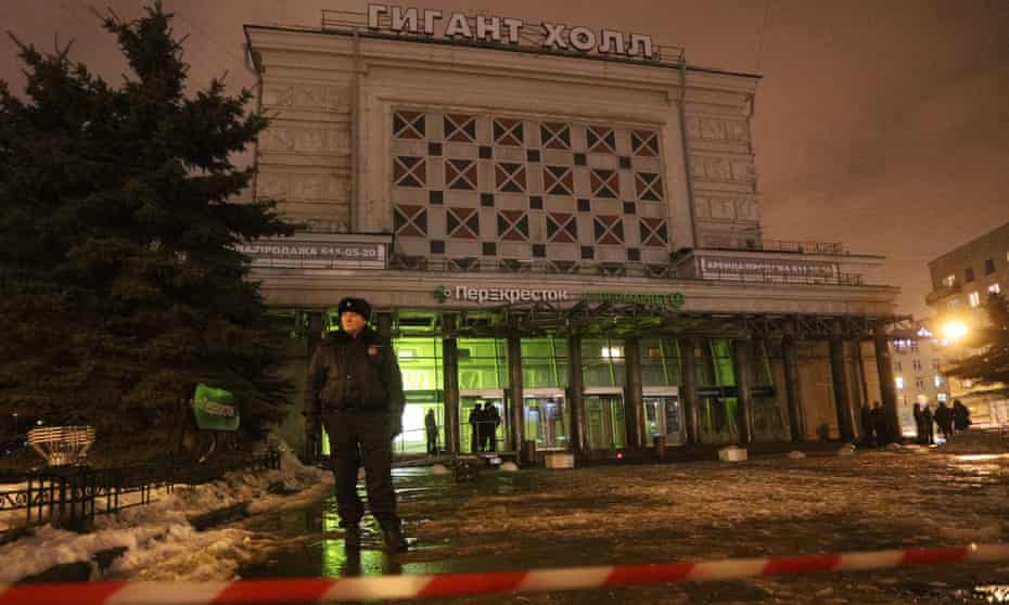 A police officer stands guard outside the supermarket in St Petersburg where a bomb exploded.