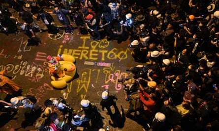 A protester dressed as a clown poses for media photographers with his duck