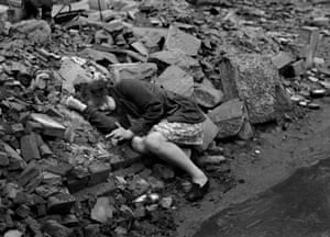 A girl cowers in rubble in Dessau, Germany, in April 1945