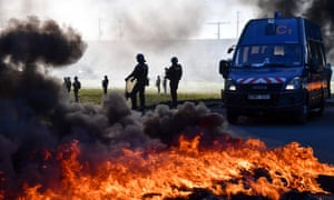 Gendarmes walk next to burning tyres as they try to remove a blockade of gilets jaunes protesters in Aimargues, near Montpellier