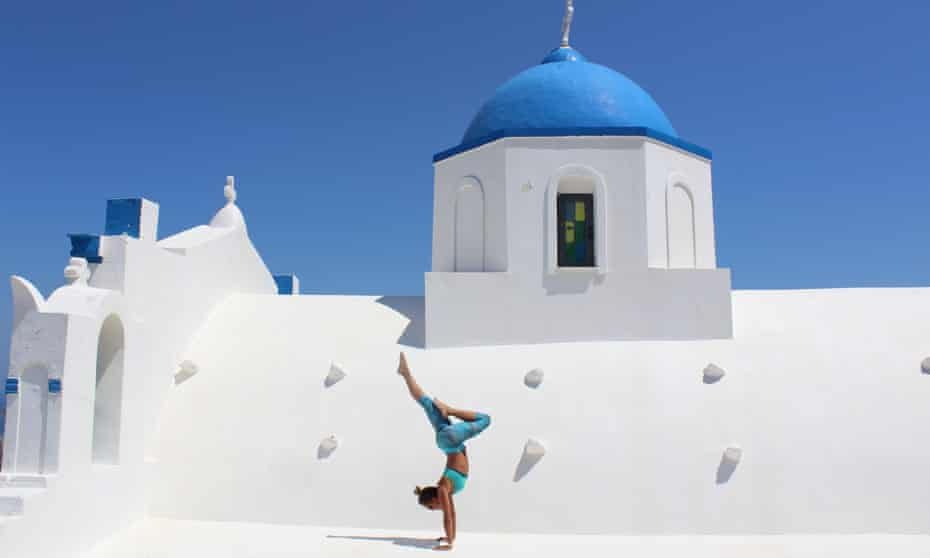 Woman practicing yoga on roof of classic blue and white Greek building in Santorini