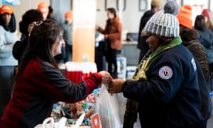 TSA worker Amelia Williams, right, is collecting food at a donation site created by the New York Food Bank in New York.