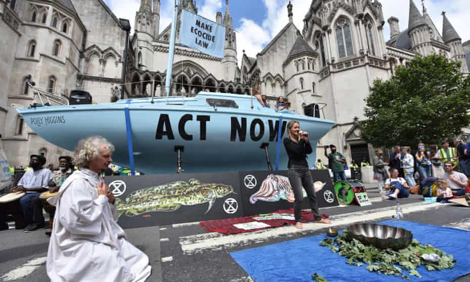 Extinction Rebellion protesters perform a water ceremony, mixing water from all over the country to be poured into the River Thames, outside the royal courts of justice in the Strand, central London.