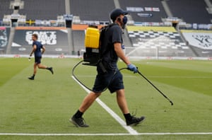 A member of the Spurs field team enters the field to disinfect the goal posts before starting the match against West Ham.