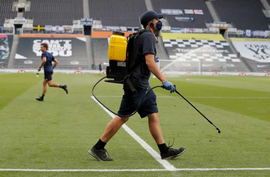 A member of the Spurs ground staff walks onto the pitch to disinfect the goal posts just before kick off in the match against West Ham.