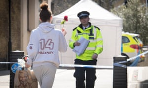 A woman brings a flower to the scene of the fatal stabbing in Link Street, Hackney.