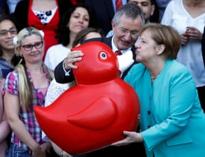 Rostock, Germany. German chancellor, Angela Merkel, receives a giant rubber duck from Arndt Rolfs, the CEO of Centogene AG as she visits biotech company