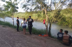 Tania Vanessa Ávalos of El Salvador, center left, is assisted by Mexican authorities after her husband and nearly two-year-old daughter were swept away by the current while trying to cross the Rio Grande to Brownsville, Texas, in Matamoros, Mexico.