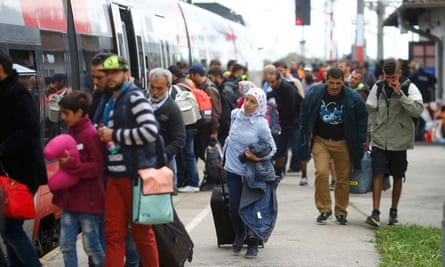 Refugees and migrants board a train at Nickelsdorf, Austria
