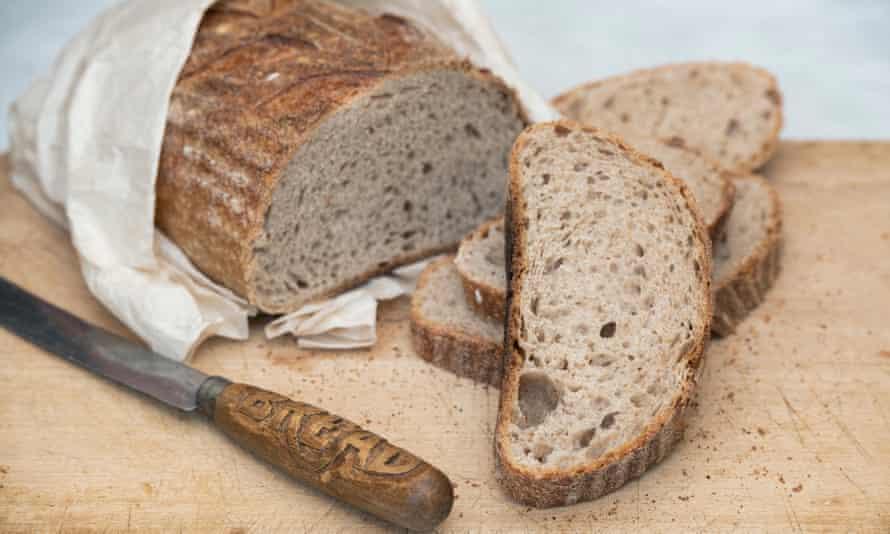 Sourdough bread with a vintage bread knife on a bread board.