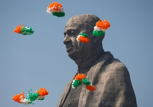 Coloured balloons float around the statue