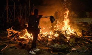 A protester pours petrol onto a burning barricade at the Chinese University of Hong Kong on Tuesday night.